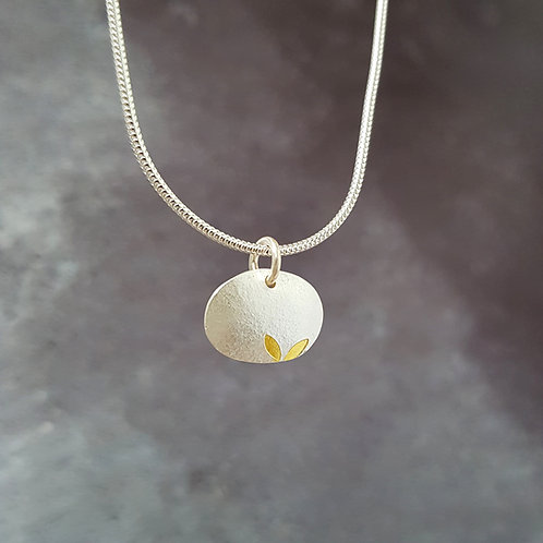 Tiny silver and gold seedling pendant