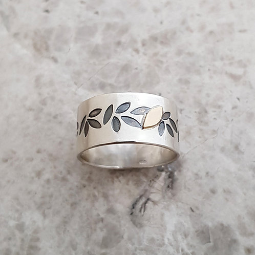 Silver ring with tiny gold leaf.