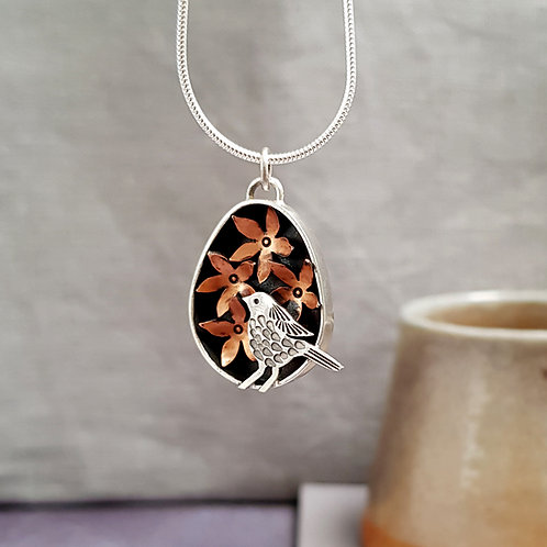 silver and copper necklace with bird and flowers