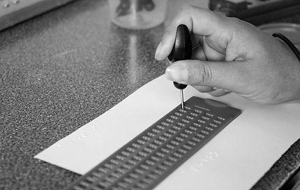 acercamiento a la mano de una persona que escribe en braille con punzón y regleta
