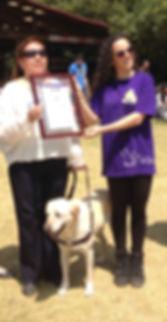 Silvia Lozada con perra guía recibiendo simbólicamente equipo de anestesia inhalada