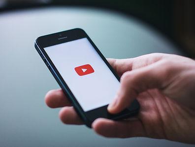 main qui tient smarphone avec page youtube