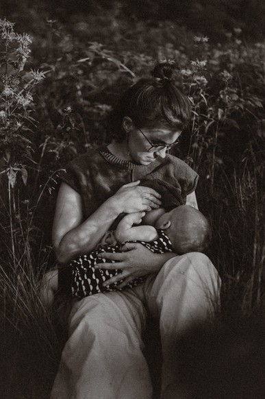 Mother nursing son in the wildflowers in black and white.