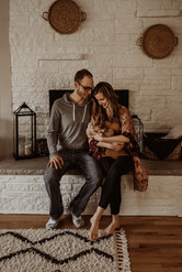 Newborn photo session in Greenfield Wisconsin. Dad and mom are sitting on fireplace and holding newborn. Mom and dad are looking down and smiling at baby. Baskets hang on the wall behind them.