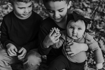 Black and white photo of siblings at Price Park in Elkhorn Wisconsin. Big brother is holding baby sister on his lap. They are sitting on a log. He is looking at her hand. Baby sister is looking at camera with serious expression on her face. Other brother is sitting on other side of big brother smiling lightly at them.