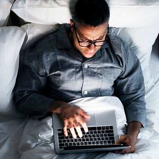 man-using-a-laptop-in-the-bed-KXWCF82_ed