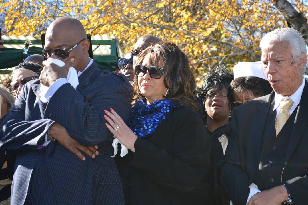 Date of Photograph: ca. November 2, 2015  Pastor Mark Henton and Lady Grace Henton pictured with others mourning at the internment of Apostle Richard D. Henton.   Physical Attributes: Color (2048 x 1365 px; 96 dpi)  Photo Credit: Courtesy of Rory Trotter Sr.  Going Home | R.D. Henton Photo Library