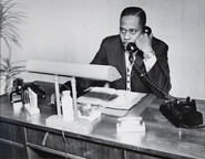 Date of Photograph: ca. 1960s  Pastor R.D. Henton shown sitting at his desk on the telephone in his office.  Physical Attributes: Black and White (4237 x 3305 px; 96 dpi)  Photo Credit: Courtesy of R.D. Henton Breakthrough Ministries.  Monument of Faith Church on Racine   R.D. Henton Photo Library.