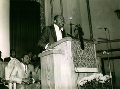 Date of Photograph: ca. 1968  Pastor R.D. Henton stands at the podium preaching at the Monument of Faith Deliverance Center with his brother Donald Henton sitting in the pulpit behind him.  Physical Attributes: Black and White (2799 x 2064 px; 96 dpi)  Photo Credit: Courtesy of R.D. Henton Breakthrough Ministries.  Monument of Faith Church on Racine   R.D. Henton Photo Library.