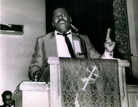 Date of Photograph: ca. 1967  Pastor R.D. Henton preaching at the Monument of Faith Deliverance Center during the Triumphant Deliverance Crusade.  Physical Attributes: Black and White (2845 x 2208 px; 96 dpi)  Photo Credit: Courtesy of R.D. Henton Breakthrough Ministries.  Monument of Faith Church on Racine   R.D. Henton Photo Library.