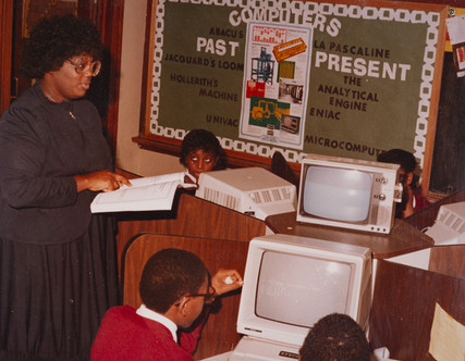 Date of Photograph: ca. 1980s  R.D. Henton Academy teacher pictured inside computer classroom giving students instructions.  Physical Attributes: Color (5344 x 4140 px; 96 dpi)  Photo Credit: Courtesy of R.D. Henton Breakthrough Ministries.  R.D. Henton Academy | R.D. Henton Photo Library