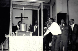 Date of Photograph: ca. 1960s  Pastor R.D. Henton preaching at the Monument of Faith Deliverance Center visually illustrating a message with a physical make-shift water drawing well and bucket.  Church ministers stand around as he makes the illustration.  Physical Attributes: Black and White (1308 x 863 px; 96 dpi)  Photo Credit: Courtesy of R.D. Henton Breakthrough Ministries.  Monument of Faith Church on Racine   R.D. Henton Photo Library.