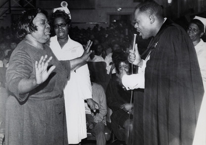 Date of Photograph: ca. 1960s  Pastor R.D. Henton pictured ministering to a woman at the Monument of Faith Deliverance Center.  Physical Attributes: Black and White (4793 x 3754 px; 96 dpi)  Photo Credit: Courtesy of R.D. Henton Breakthrough Ministries.  Monument of Faith Church on Racine   R.D. Henton Photo Library.