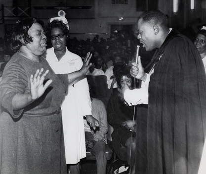 Date of Photograph: ca. 1960s  Pastor R.D. Henton pictured ministering to a woman at the Monument of Faith Deliverance Center.  Physical Attributes: Black and White (4793 x 3754 px; 96 dpi)  Photo Credit: Courtesy of R.D. Henton Breakthrough Ministries.  Monument of Faith Church on Racine | R.D. Henton Photo Library.