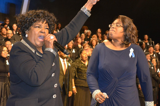 Date of Photograph: ca. October 31, 2015  Pastor Shirley Casear and Sis. Tanya Ray singing together at the National Homegoing Celebration of Apostle Richard D. Henton, held at the House of Hope in Chicago IL.  The Monument of Faith Mass Choir pictured in the background.  Physical Attributes: Color (2048 x 1365 px; 96 dpi)  Photo Credit: Courtesy of Rory Trotter Sr.  Going Home | R.D. Henton Photo Library
