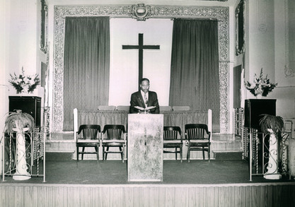 Date of Photograph: ca. 1960s  Pastor R.D. Henton shown in an empty pulpit at the Monument of Faith Deliverance Center, standing behind the podium holding an open bible.  Physical Attributes: Black and White (2792 x 2186 px; 96 dpi)  Photo Credit: Courtesy of R.D. Henton Breakthrough Ministries.  Monument of Faith Church on Racine   R.D. Henton Photo Library.