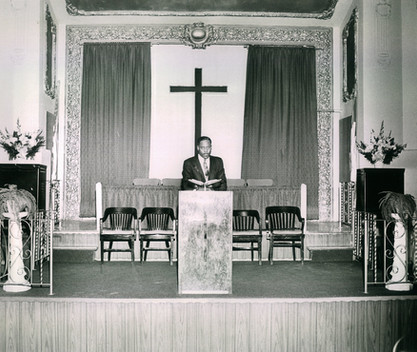Date of Photograph: ca. 1960s  Pastor R.D. Henton shown in an empty pulpit at the Monument of Faith Deliverance Center, standing behind the podium holding an open bible.  Physical Attributes: Black and White (2792 x 2186 px; 96 dpi)  Photo Credit: Courtesy of R.D. Henton Breakthrough Ministries.  Monument of Faith Church on Racine | R.D. Henton Photo Library.
