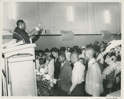 Date of Photograph: ca. 1960s  Pastor R.D. Henton pictured with a crowd gathered at the altar as he extends an invitation at the Monument of Faith Deliverance Center.  Physical Attributes: Black and White (1343 x 659 px; 96 dpi)  Photo Credit: Courtesy of R.D. Henton Breakthrough Ministries.  Monument of Faith Church on Racine   R.D. Henton Photo Library.