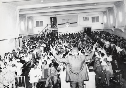 Date of Photograph: ca. 1960s  Pastor R.D. Henton shown standing at the podium looking out at the congregation with hands uplifited inside the Monument of Faith Deliverance Center from the front to the back.  Physical Attributes: Black and White (5708 x 4311 px; 96 dpi)  Photo Credit: Courtesy of R.D. Henton Breakthrough Ministries.  Monument of Faith Church on Racine   R.D. Henton Photo Library.