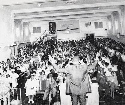Date of Photograph: ca. 1960s  Pastor R.D. Henton shown standing at the podium looking out at the congregation with hands uplifited inside the Monument of Faith Deliverance Center from the front to the back.  Physical Attributes: Black and White (5708 x 4311 px; 96 dpi)  Photo Credit: Courtesy of R.D. Henton Breakthrough Ministries.  Monument of Faith Church on Racine | R.D. Henton Photo Library.