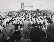Date of Photograph: ca. 1960s  Pastor R.D. Henton stands at the podium as the congregation has uplifted hands in prayer.  Physical Attributes: Black and White (5803 x 4522 px; 96 dpi)  Photo Credit: Courtesy of R.D. Henton Breakthrough Ministries.  Monument of Faith Church on Racine   R.D. Henton Photo Library.