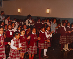Date of Photograph: ca. 1980s  Inside the EE Cleveland Auditorium showing students and teachers clapping and singing.  Physical Attributes: Color (5663 x 4574 px; 96 dpi)  Photo Credit: Courtesy of R.D. Henton Breakthrough Ministries.  R.D. Henton Academy | R.D. Henton Photo Library