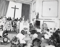 Date of Photograph: ca. 1960s  Pastor R.D. Henton preaching at the Monument of Faith Deliverance Center.  Physical Attributes: Black and White (5560 x 4345 px; 96 dpi)  Photo Credit: Courtesy of R.D. Henton Breakthrough Ministries.  Monument of Faith Church on Racine   R.D. Henton Photo Library.