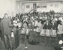 Date of Photograph: ca. 1960s  Pastor R.D. Henton standing at the podium looking out at the congregation standing, some with uplifted hands, clapping and praising God.  Physical Attributes: Black and White (11383 x 8990 px; 96 dpi)  Photo Credit: Courtesy of R.D. Henton Breakthrough Ministries.  Monument of Faith Church on Racine   R.D. Henton Photo Library.