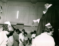Date of Photograph: ca. 1960s  Pastor R.D. Henton stands praying over the congregation with their heads bowed, at the Monument of Faith Deliverance Center.  Physical Attributes: Black and White (2775 x 2188 px; 96 dpi)  Photo Credit: Courtesy of R.D. Henton Breakthrough Ministries.  Monument of Faith Church on Racine   R.D. Henton Photo Library.