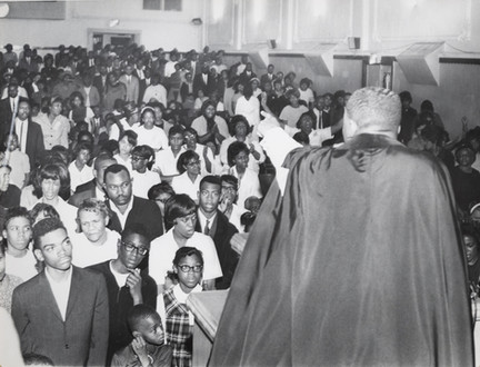 Date of Photograph: ca. 1960s  Pastor R.D. Henton pictured with a crowd gathered at the altar as he extends an invitation at the Monument of Faith Deliverance Center.  Physical Attributes: Black and White (4810 x 3669 px; 96 dpi)  Photo Credit: Courtesy of R.D. Henton Breakthrough Ministries.  Monument of Faith Church on Racine   R.D. Henton Photo Library.
