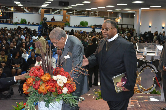 Date of Photograph: ca. October 30, 2015  Dr. Clay Evans (left) being assisted from the podium by Pastor Ray Berryhill (right) after giving remarks during the Monument of Faith Church Family Homegoing Celebration for Apostle Richard D. Henton  Physical Attributes: Color (2048 x 1365 px; 96 dpi)  Photo Credit: Courtesy of Rory Trotter Sr.  Going Home | R.D. Henton Photo Library