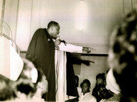 Date of Photograph: ca. 1960s  Pastor R.D. Henton standing in the pulpit shown pointing into the congregation.   Physical Attributes: Black and White (2821 x 2096 px; 96 dpi)  Photo Credit: Courtesy of R.D. Henton Breakthrough Ministries.  Monument of Faith Church on Racine   R.D. Henton Photo Library.