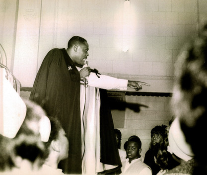 Date of Photograph: ca. 1960s  Pastor R.D. Henton standing in the pulpit shown pointing into the congregation.   Physical Attributes: Black and White (2821 x 2096 px; 96 dpi)  Photo Credit: Courtesy of R.D. Henton Breakthrough Ministries.  Monument of Faith Church on Racine | R.D. Henton Photo Library.