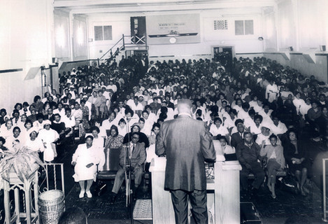 Date of Photograph: ca. 1960s  Pastor R.D. Henton standing at the podium looking out at the congregation at the Monument of Faith Deliverance Center from the front to the back.  Physical Attributes: Black and White (2837 x 1935 px; 96 dpi)  Photo Credit: Courtesy of R.D. Henton Breakthrough Ministries.  Monument of Faith Church on Racine   R.D. Henton Photo Library.