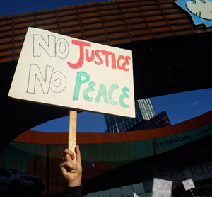 "A sign reading ""No Justice No Peace"" is held up high."