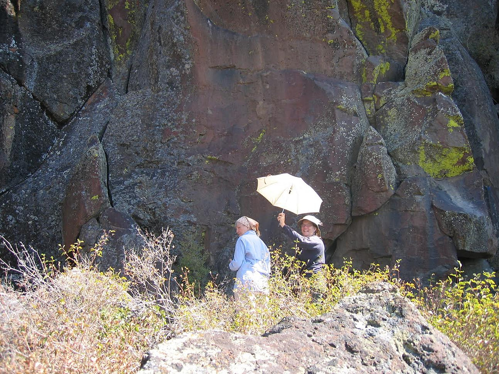 Carolynne, in blue, photographing rock art at Indian Writing Water Hole