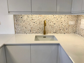 White handless kitchen with brass fittings, quartz worktop and Italian terrazzo tiles