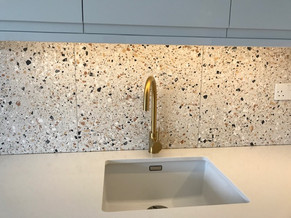 White handless kitchen with brass fittings, quartz worktop and Italian terrazzo tiles