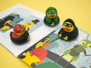 """Image of the three rubber ducks accompanying """"Duckland's Superheroes Stop a Quacktastrophe"""" on top of a spread."""
