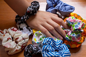 Girl's hand with textile scrunchies, hai