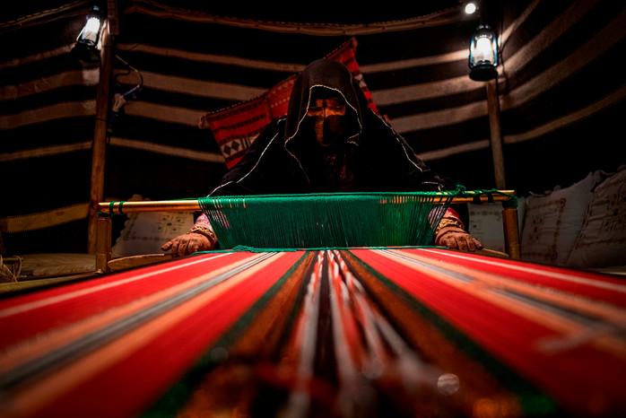 Arab Women perform a traditional weaving.