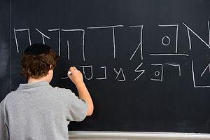 Boy Writing Hebrew Letters on Blackboard