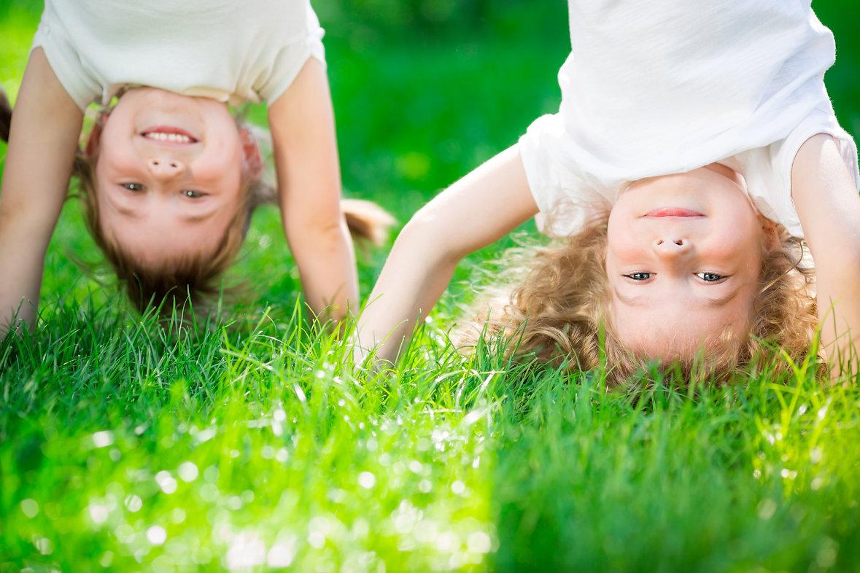 Happy children standing upside down on g