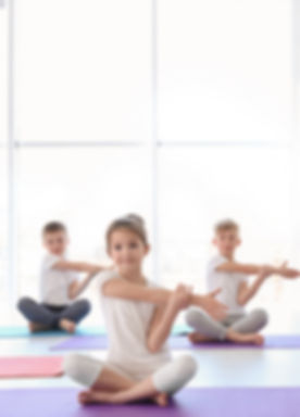 Little children practicing yoga in gym_e