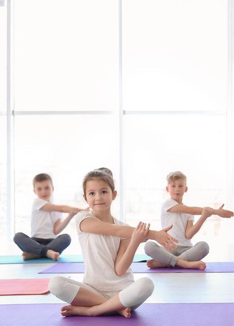 Little children practicing yoga in gym_e