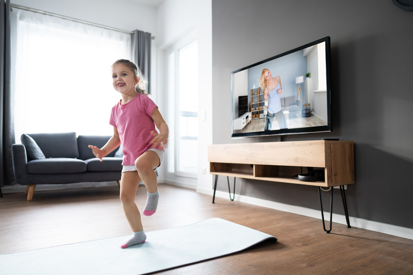 Kid Doing Online TV Fitness Exercise At