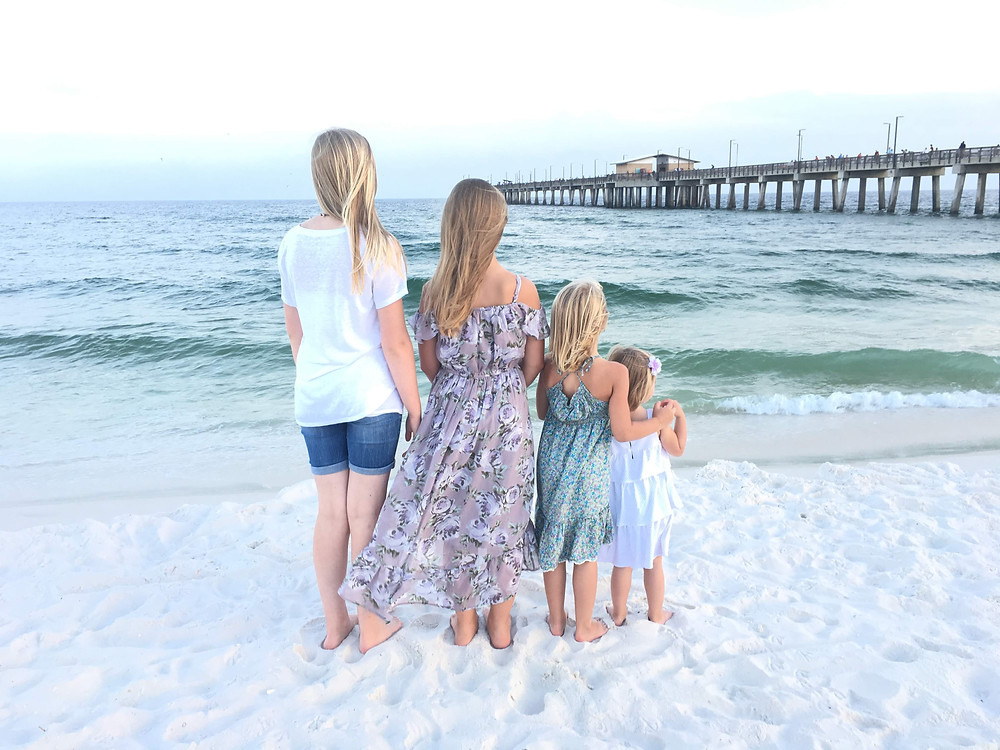 Four girls in front of a pier on the beach