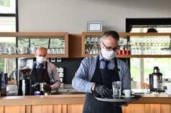 waiter in a medical protective mask serv