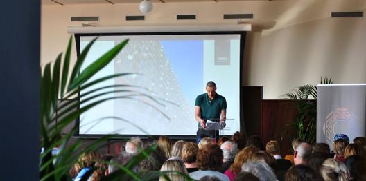 Arjen Scholten voor een Overvechtse flat. Hij schetst de context rondom geletterde thuisomgeving en hoe moeilijk het is om dit de bewerkstelligen bij de doelgroep. Een introductie op de presentatie van gedragswetenschapper Reint Jan Renes.