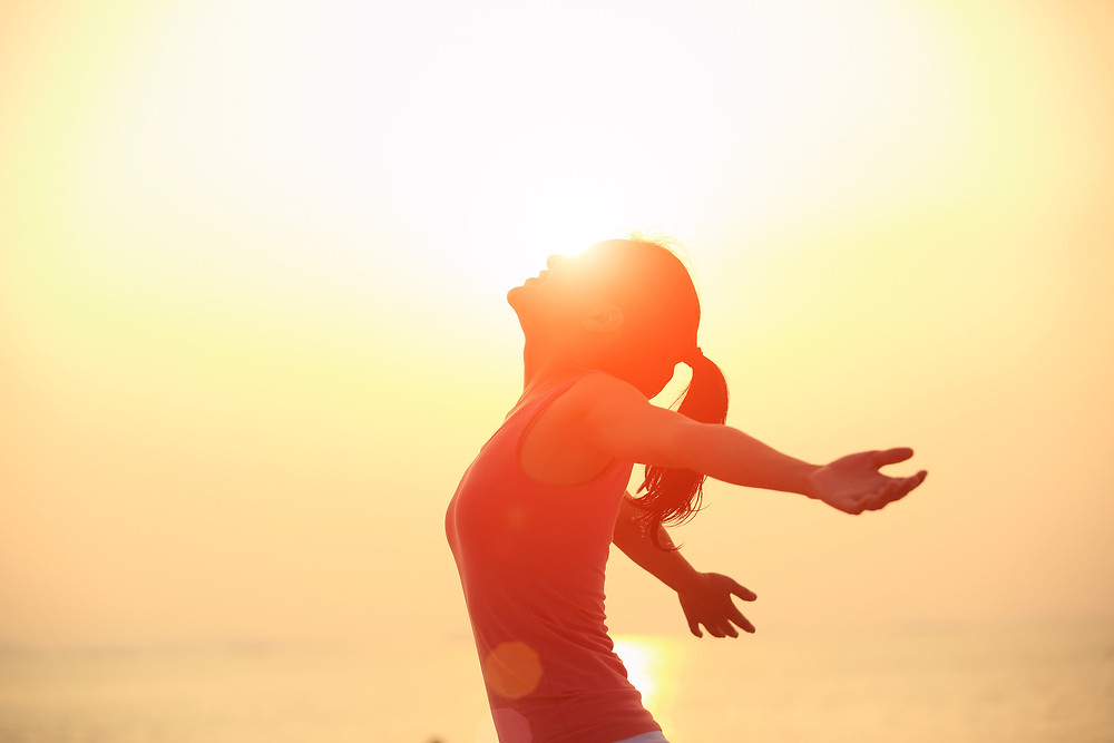 girl stretching in sunshine arms open silhouette
